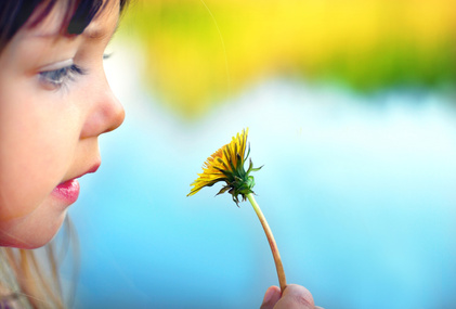 Cute girl with dandelion, focus on dandelion